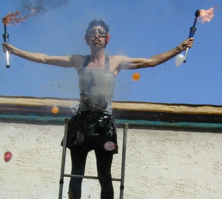 Dexter Tripp balancing on a ladder while firecrackers duct-taped to him explode and people throw water balloons at him