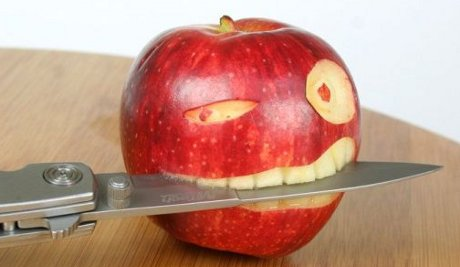 apple carved into a pirate head, with a knife in its teeth