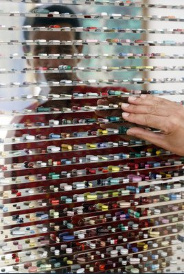 art depicting a human behind a bunch of transparent boxes, each with a pill in it