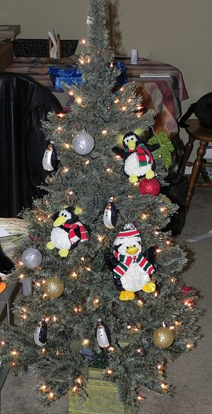 Christmas tree with a bunch of penguin ornaments hanging from it