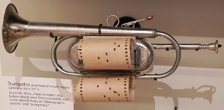 old cornet operating on the principle of the player piano, where a paper roll with holes opens and closes the valves of the cornet